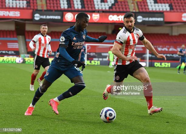 Nicolas Pepe of Arsenal takes on Enda Stevens of Sheffield United during the Premier League match between Sheffield United and Arsenal at Bramall...