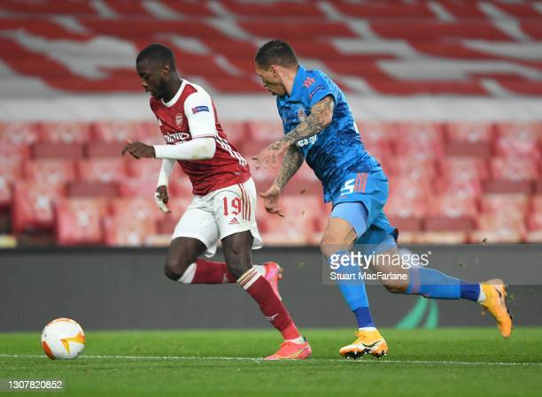 Nicolas Pepe of Arsenal takes on Jose Holebas of Olympiacos during the UEFA Europa League Round of 16 Second Leg match between Arsenal and Olympiacos...