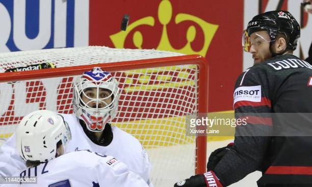 Nicolas Ritz and Henri-Corentin Buysse of France battle the puck with Sean Couturier of Canada during the 2019 IIHF Ice Hockey World Championship...