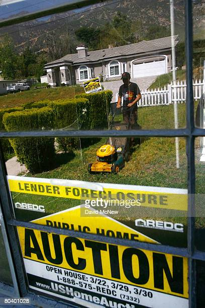 Nicolas Rosas is reflected in a window as he mows grass and weeds to prepare a house to be sold on March 27, 2008 in Altadena, California. Houses are...