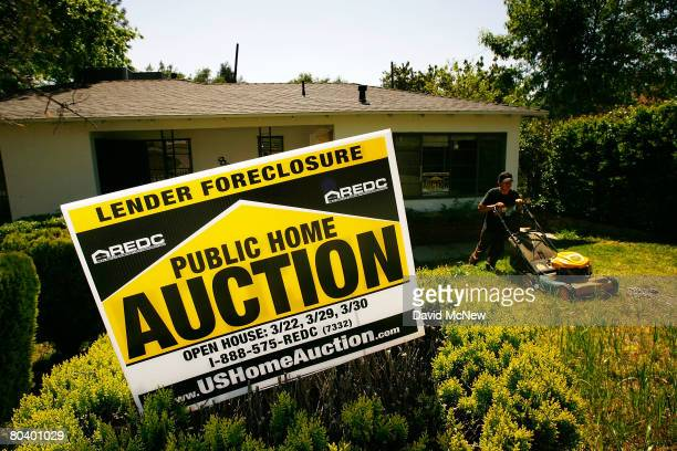 Nicolas Rosas mows grass and weeds to prepare a house to be sold on March 27 2008 in Altadena California Houses are being prepared for an 11day...