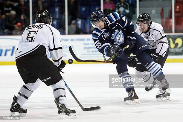 Nicolas Roy of the Chicoutimi Sagueneens shoots the puck deep as Elie Berube of the Gatineau Olympiques defends on February 20 2015 at Robert Guertin...