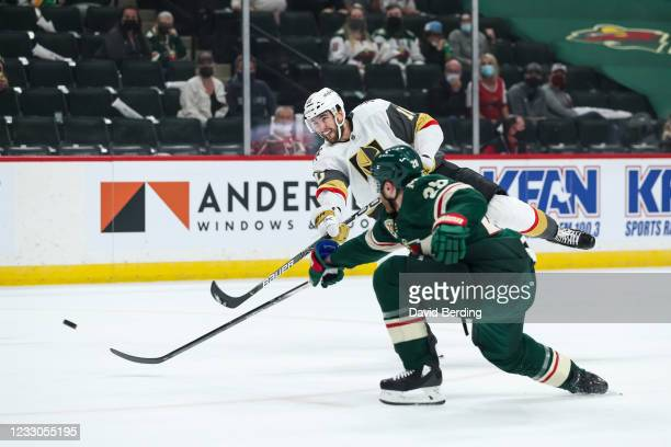Nicolas Roy of the Vegas Golden Knights shoots the puck to score a goal while Ian Cole of the Minnesota Wild defends in the first period in Game Four...