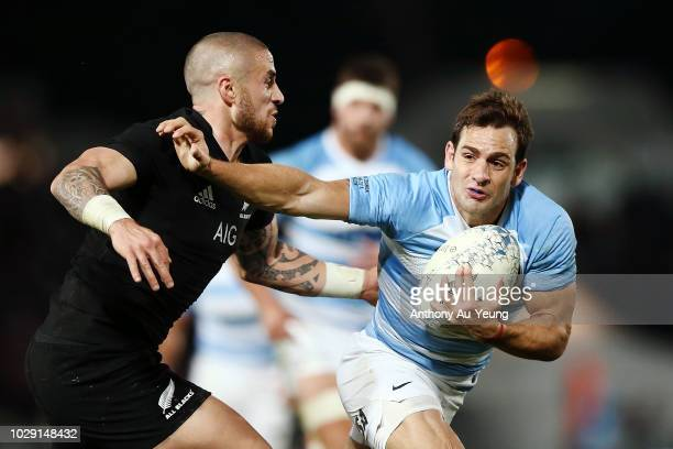 Nicolas Sanchez of Argentina fends against TJ Perenara of the All Blacks during The Rugby Championship match between the New Zealand All Blacks and...