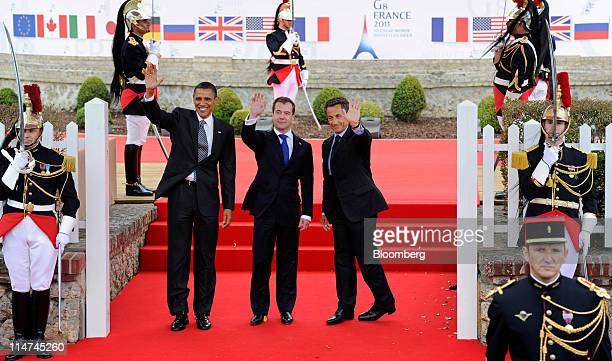 Nicolas Sarkozy France's president right stands with US President Barack Obama left and Dmitry Medvedev Russia's president at the Group of Eight...