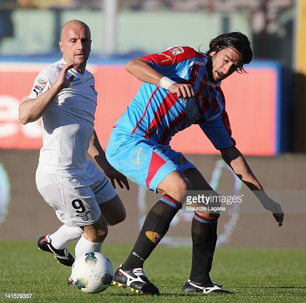 Nicolas Spolli of Catania competes for the ball with Tommaso Rocchi of Lazio during the Serie A match between Catania Calcio and SS Lazio at Stadio...