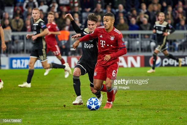 Nicolas Tagliafico of Ajax Amsterdam and Thiago of Bayern Muenchen battle for the ball during the Group E match of the UEFA Champions League between...