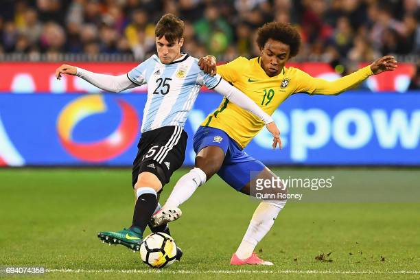 Nicolas Tagliafico of Argentina and Willian Silva of Brazil compete for the ball during the Brazil Global Tour match between Brazil and Argentina at...
