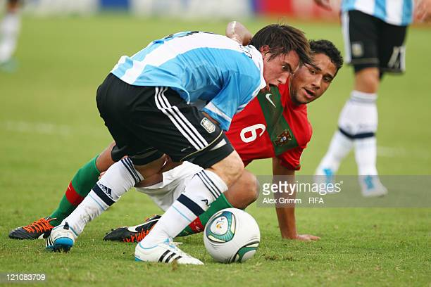 Nicolas Tagliafico of Argentina is challenged by Julio Alves of Portugal during the FIFA U20 World Cup 2011 quarter final match between Portugal and...