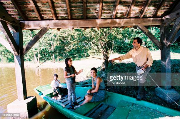 Nicolas Vanier with his wife Diane and their two children Montaine and Loup fish on a rowing boat on the Sologne river