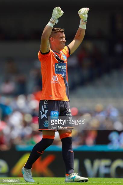 Nicolas Vikonis of Puebla celebrates the first goal of his team scored by Lucas Cavallni during the 15th round match between Pumas UNAM and Puebla as...