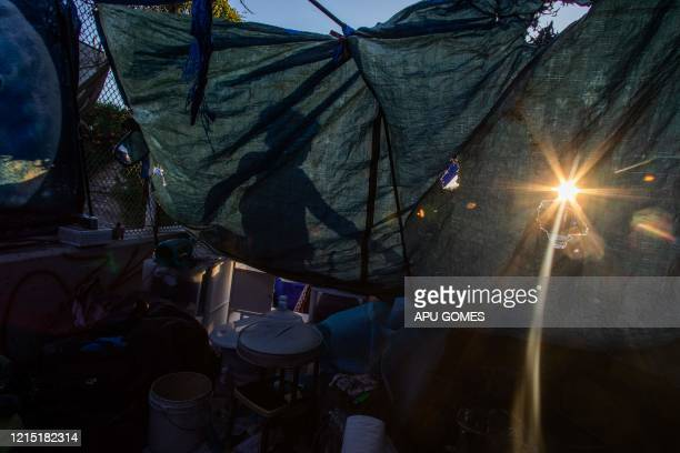 Nicole 40 yearsold fixes her tent over the bridge of the 110 Freeway during the novel Coronavirus COVID19 pandemic in Los Angeles California on May...