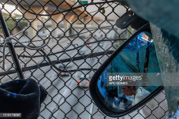 Nicole 40 yearsold is seen through a mirror inside her tent over a bridge at the Freeway during the novel Coronavirus COVID19 pandemic in Los Angeles...