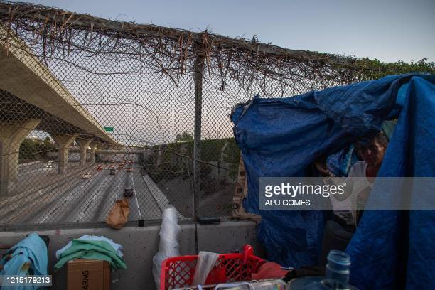 TOPSHOT Nicole 40 yearsold leaves her tent over a bridge of the 110 Freeway during the novel Coronavirus COVID19 pandemic in Los Angeles California...