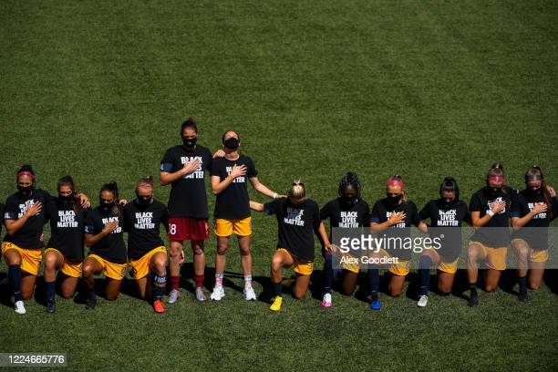 Nicole Barnhart and Kelley O'Hara of Utah Royals FC stand as teammates kneel for the national anthem before a game against the Sky Blue FC on day 4...