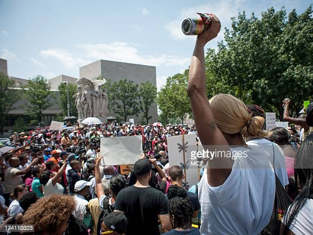 Nicole Cowan of Oxon Hill Maryland holds a can of ice tea and a bag of Skittles aloft during a Justice for Trayvon rally outside the E Barrett...
