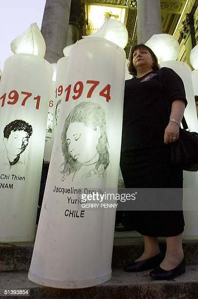 Nicole Drouilly holds a candle in honour of her sister Jacqueline one of more than a thousand missing in Chile as Amnesty International the world's...
