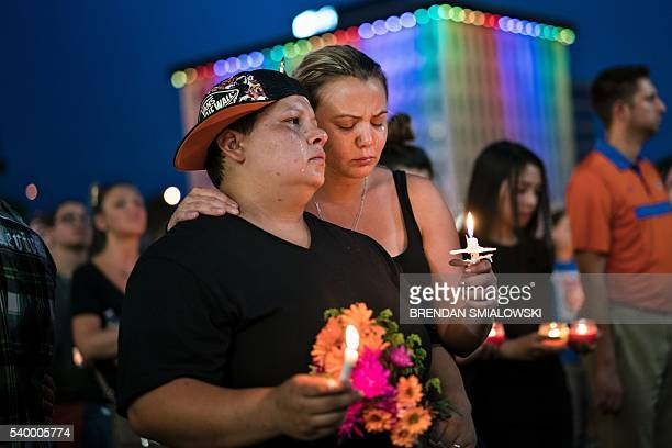 TOPSHOT Nicole Edwards and her wife Kellie Edwards observe a moment of silence during a vigil outside the Dr Phillips Center for the Performing Arts...
