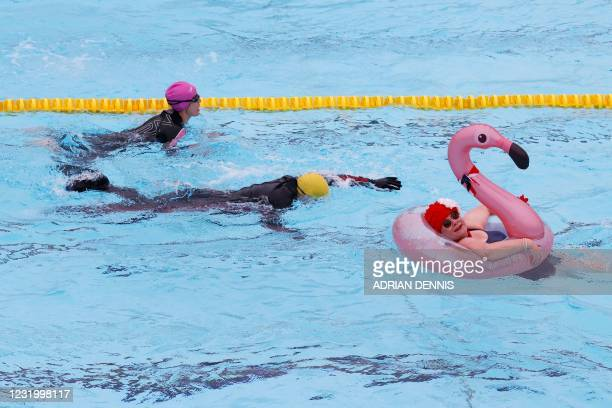 Nicole Foster swims with the aid of an inflatable flamingo at Hillingdon lido in west London as Covid-19 lockdown restrictions ease to allow outdoor...