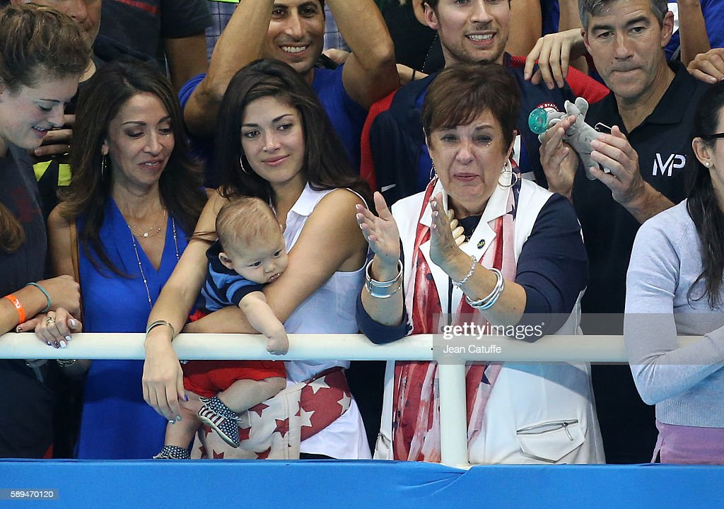 Nicole Johnson, fiancee of Michael Phelps - holding their baby son Boomer Phelps -, and Debbie Phelps, Michael's mother smile at Michael Phelps and teammates during the lap of honor following the gold medal ceremony for the Men's 4 x 100m Medley Relay on day 8 of the Rio 2016 Olympic Games at Olympic Aquatics Stadium on August 13, 2016 in Rio de Janeiro, Brazil.