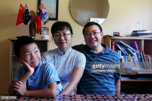 Nicole Li Charlie He and son James He originally from Beijing sit at a dining table in their new home on January 25 2017 in Tamworth Australia...