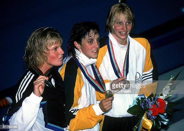 Nicole Livingstone of Australia celebrate's with her gold medal after winning the Women's 100m Backstroke Final during the 1990 Commonwealth Games in...