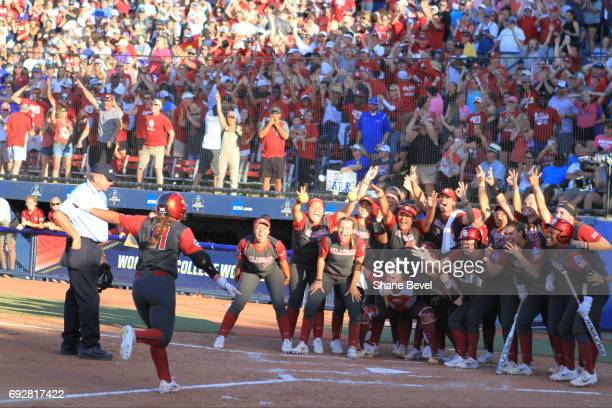 Nicole Mendes of The University of Oklahoma meets her team at home plate as she scores a run during the Division I Women's Softball Championship held...