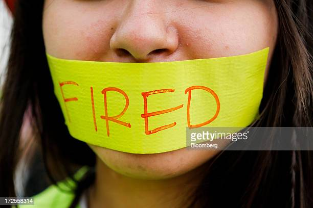Nicole Mora a WalMart Stores Inc employee fired from the Lakewood location wears a piece of tape across her mouth during a demonstration outside a...
