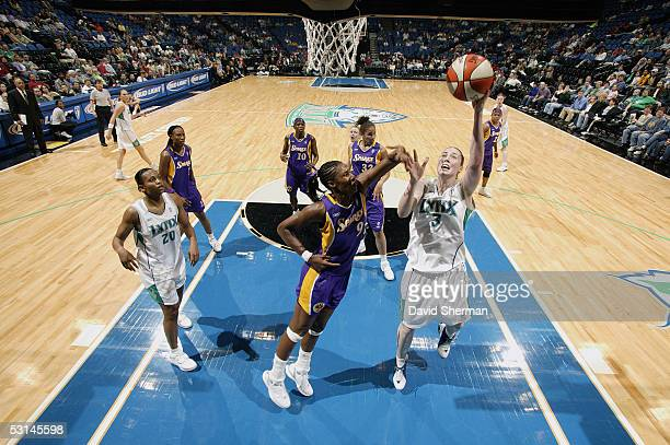 Nicole Ohlde of the Minnesota Lynx shoots a layup against Lisa Leslie of the Los Angeles Sparks on May 25 2005 at the Target Center in Minneapolis...