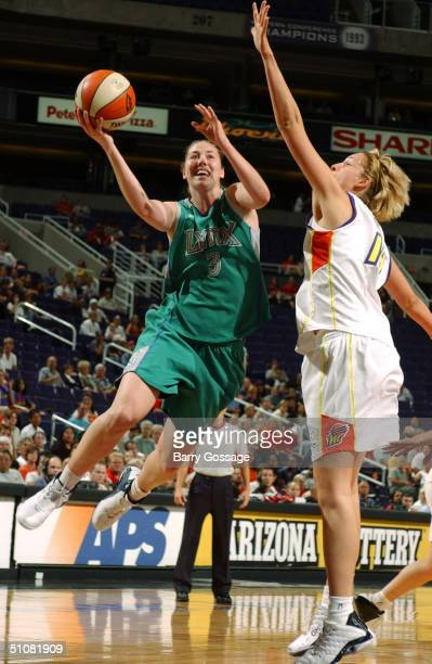 Nicole Ohlde of the Minnesota Lynx takes the ball up against Slobodanka Tuvic of the Phoenix Mercury during a WNBA game played on June 22 2004 at...