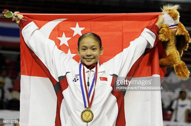 Nicole Tay Jia Hui of Singapore celebrates with her national flag after winning the floor exercise for the finals Women's Artistic Gymnastics...