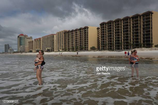 Nicole Wall holds Callen Wall along with Jenny Bradley enjoy the gulf water a day after Hurricane Sally passed through the area on September 17 2020...