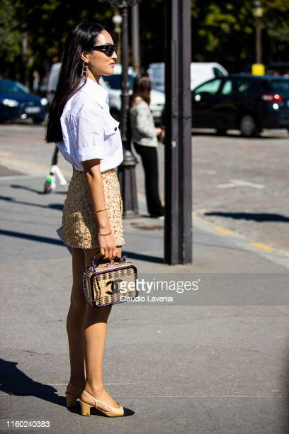 Nicole Warne, wearing a white shirt, Chanel beige skirt, Chanel heels and Chanel straw bag, is seen outside Chanel show during Paris Fashion Week -...