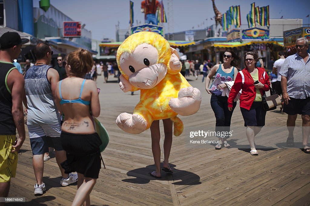 Nicole Zupp carries a stuffed monkey prize on the boardwalk at Seaside Heights on the first weekend of New Jersey beaches re-opening to the public on May 27, 2013 in Seaside Heights, New Jersey. The region continues to recover and rebuild after Hurricane Sandy devastated parts of the coastline.
