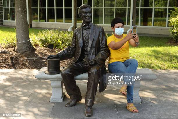 Nicolette Holness of Bismarck, North Dakota, takes a selfie with a statue of President Abraham Lincoln outside the visitor center at the Gettysburg...
