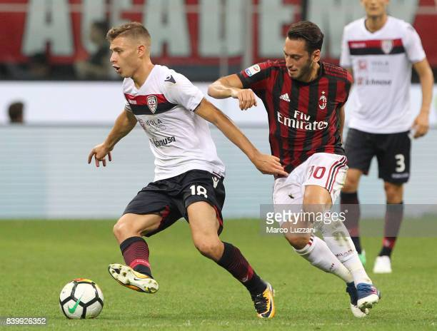 Nicolo Barella of Cagliari Calcio competes for the ball with of Hakan Calhanoglu AC Milan during the Serie A match between AC Milan and Cagliari...