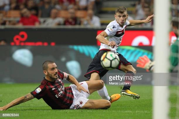 Nicolo Barella of Cagliari Calcio is challenged by Leonardo Bonucci of AC Milan during the Serie A match between AC Milan and Cagliari Calcio at...