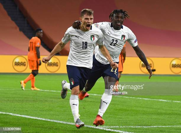 Nicolo Barella of Italy celebrates with team-mate Moise Kean after scoring the opening goal during the UEFA Nations League group stage match between...