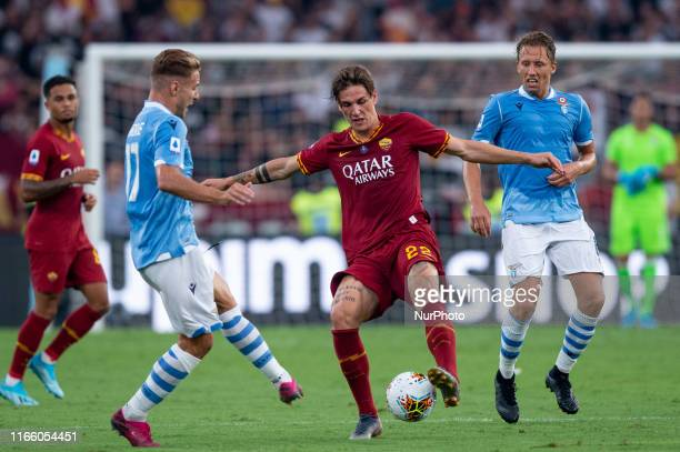 Nicolo' Zaniolo of AS Roma is challenged by Ciro Immobile of SS Lazio during the Serie A match between Lazio and AS Roma at Stadio Olimpico Rome...