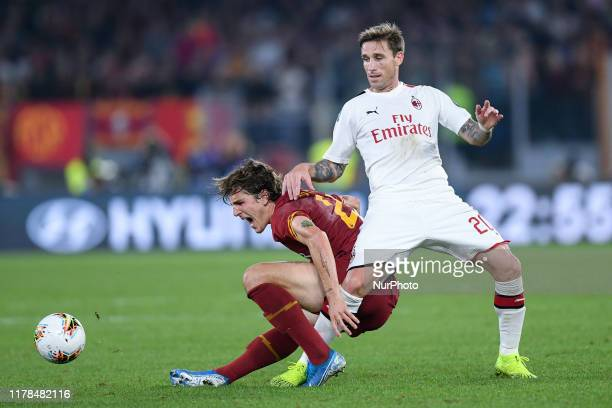 Nicolo' Zaniolo of AS Roma is challenged by Lucas Biglia of AC Milan during the Serie A match between AS Roma and AC Milan at Stadio Olimpico, Rome,...