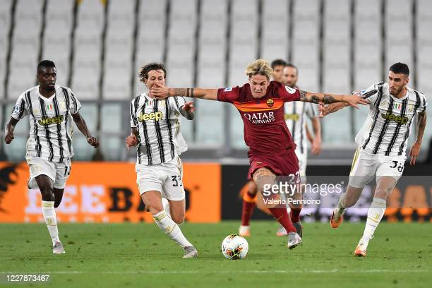 Nicolo Zaniolo of AS Roma is challenged by Simone Muratore and Federico Bernardeschi of Juventus during the Serie A match between Juventus and AS...