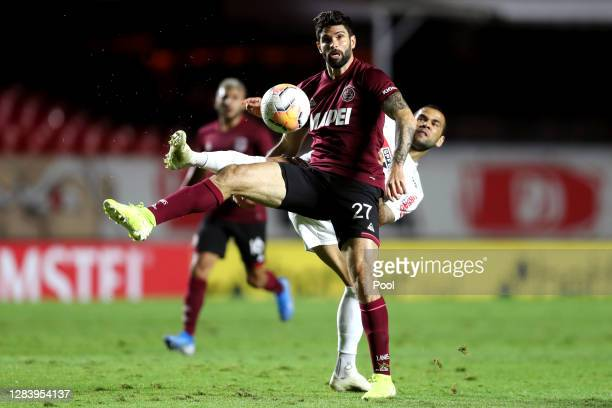Nicolás Orsini of Lanus fights for the ball with Dani Alves of Sao Paulo during a second leg match of Copa CONMEBOL Sudamericana second round between...