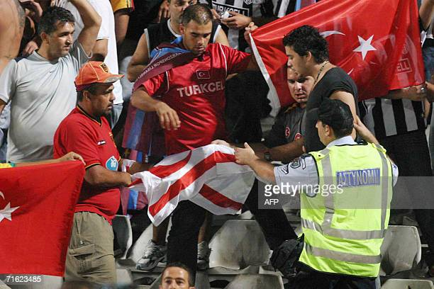 A Greek Cypriot policeman asks Turkish Cypriot fans to put down the flag of the breakaway Turkish Republic of Northern Cyprus while others hold up a...