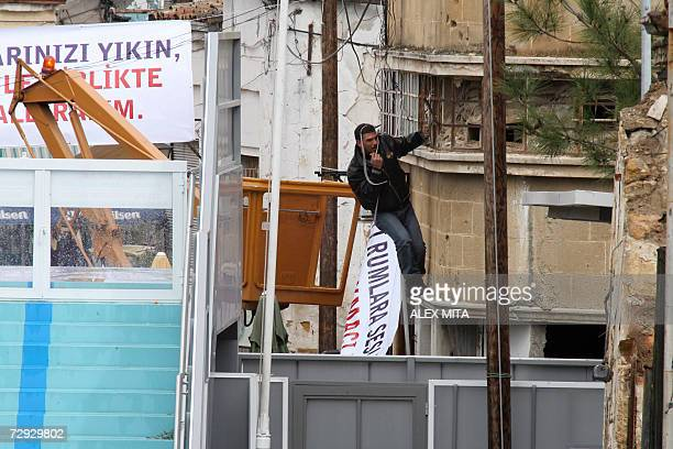 A Turkish Cypriot member of the National People's Movement hangs a banner during a protest against demolishing an elevated walkway on a street...