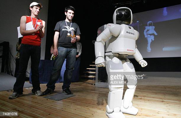 Honda's humanoid robot ASIMO walks on stage after presenting a science award for robotics to two high school students at an event at the University...