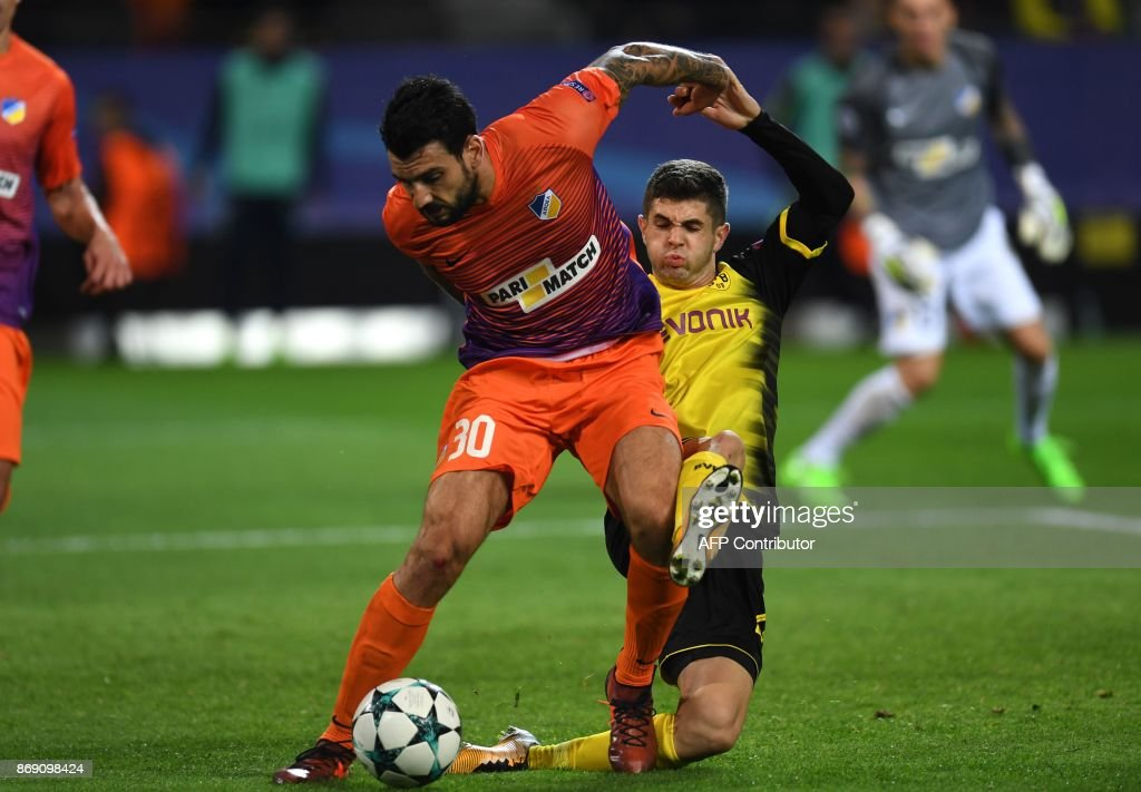 Nicosia's Cypriot defender Georgios Merkis (L) and Dortmund's midfielder Dortmund's US midfielder Christian Pulisic vie for the ball during the UEFA Champions League Group H football match BVB Borussia Dortmund v Apoel Nicosia on November 1, 2017 in Dortmund, western Germany. /