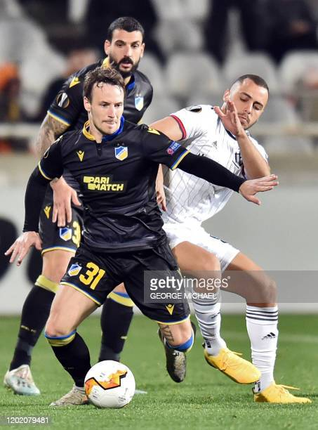 Nicosia's Danish midfielder Mike Jensen dribbles the ball past FC Basel's Brazilian forward Arthur Cabral during the Europa League last 32 first leg...