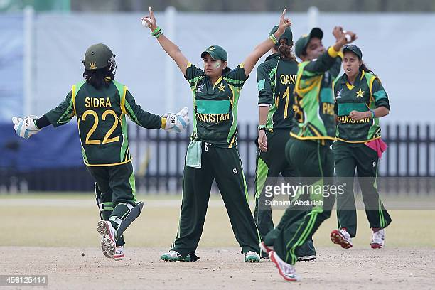 Nida Rashid of Pakistan celebrates with teammates after she bowls out Nuzhat Tasnia of Bangladesh during the cricket women's final match between...