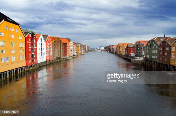 nidelva river amidst houses against cloudy sky - trondheim stock pictures, royalty-free photos & images