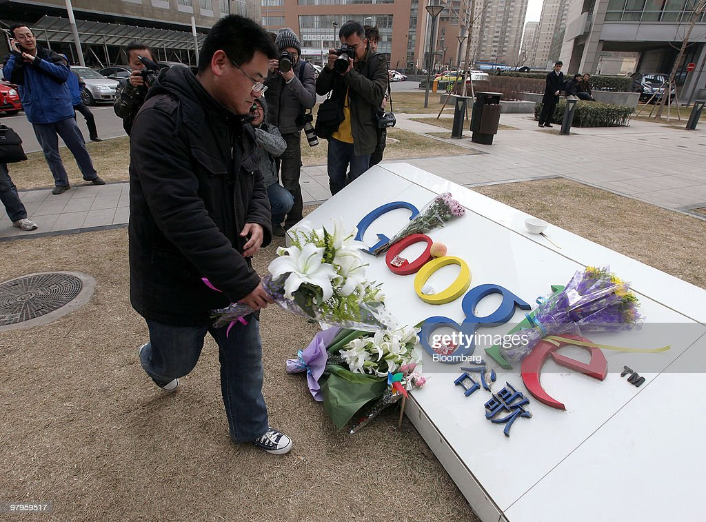 Nie Xing makes an offering of flowers outside the Google Inc. offices in Beijing, China, on Tuesday, March 23, 2010. Google Inc., following through on a pledge to stop censoring search results in China, began serving mainland Chinese users via its unfiltered Hong Kong site, a move that could prompt the government to block the service. Photographer: Doug Kanter/Bloomberg via Getty Images